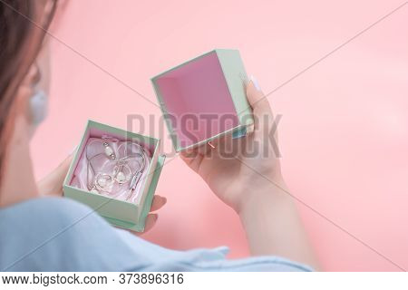 Young Woman Opens A Jewelry Gift, In The Gift Box Silver Jewelry. Present Concept, Woman Holding An
