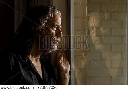 Man In Self Isolation, Stay Home Concept, Thinking Man's Reflection In Glass Window Of Brick House,