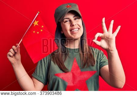 Beautiful patriotic woman wearing t-shirt with red star communist symbol holding china flag doing ok sign with fingers, smiling friendly gesturing excellent symbol