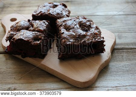 Brownies With Cherries On A Cut Board. Close-up Of Handmade Chocolate Cake On Wooden Table Backgroun