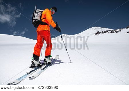 A Skier In An Orange Suit Skis In A Mountain Off-piste Skiing In The Northern Caucasus Of Mount Elbr