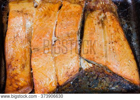 Baked Pieces Of The Trout Fillet On The Rustic Metal Oven Tray, Top View Close-up, Background