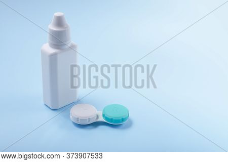 Contact Lenses And Lens Liquid On A Blue Background. Bottle With Lens Solution And Container For Con