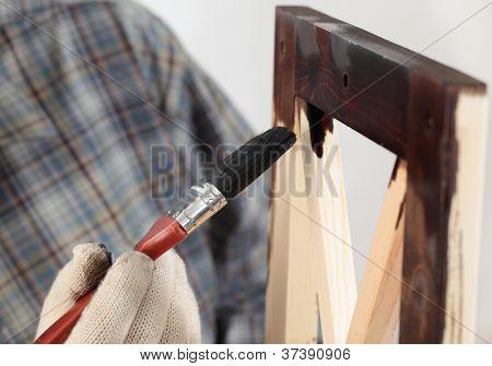 Man varnishing a wooden part of furniture using paintbrush