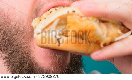 Close Up Of A Man Biting A Burger On A Chroma Key. The Concept Of Unhealthy And Unhealthy Diets, Hig