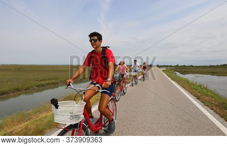 Cheerful Family Cycling Pedals On The Bike Path Near The Island Of Venice In Summer