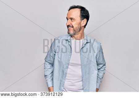 Middle age handsome man wearing casual denim shirt standing over isolated white background looking to side, relax profile pose with natural face and confident smile.
