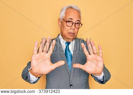 Middle age senior grey-haired handsome business man wearing glasses over yellow background Moving away hands palms showing refusal and denial with afraid and disgusting expression. Stop and forbidden.