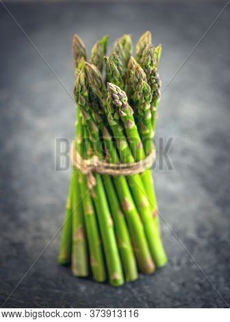 Asparagus. Fresh raw organic green Asparagus sprouts closeup. Over wooden table. Healthy vegetarian food. Raw vegetables, market. Healthy eating, diet, dieting concept