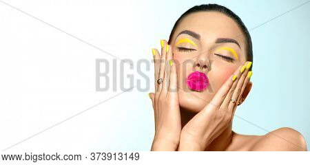 Beauty model girl with fashion make-up, Bright yellow eye line and nails, trendy manicure. Eye make-up creative ideas. Summer makeup. Kiss gesture. Beautiful young woman portrait. Face closeup