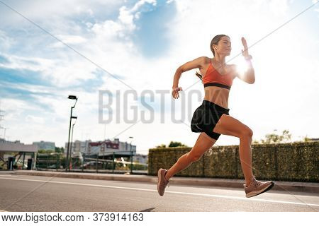 Young Woman Sprinting In The Morning Outdoors. Side View Of Female Runner Working Out In The City Wi