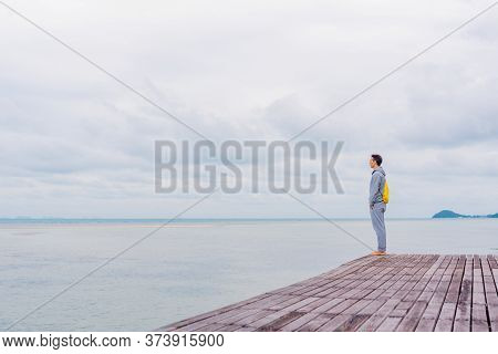 A Man In A Gray Tracksuit Stands On The Edge Of A Pier In Thailand, A Person Looks Into The Distance