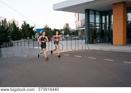Young Woman Running On Sidewalk In Morning. Health Conscious Concept. Healthy Active Lifestyle. Acti