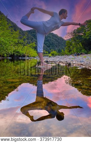 Beautiful Young Woman Performing Yoga And Meditating On A Rock In A Mountain River Under A Dramatic