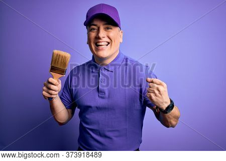 Young modern decorator painter man holding paint brush over purple background screaming proud and celebrating victory and success very excited, cheering emotion
