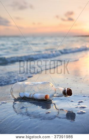 Message in a bottle on sandy shore at sunset
