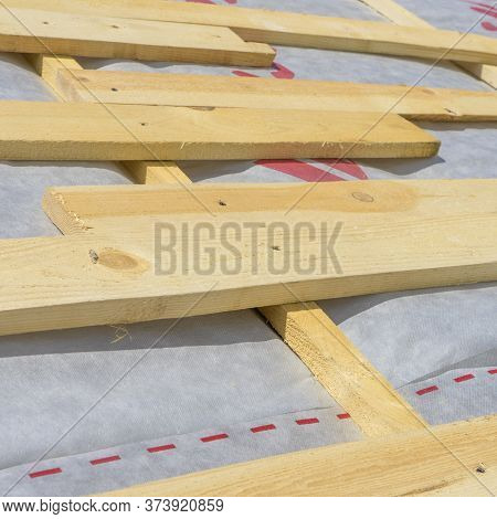 Installation Of Wooden Rafters During The Construction Of The Roof Frame, A Waterproofing Film Is St