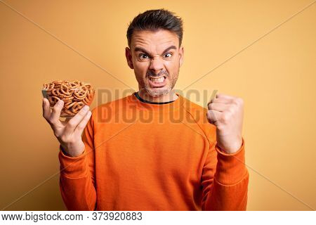 Young handsome man holding bowl with german baked pretzels over yellow background annoyed and frustrated shouting with anger, crazy and yelling with raised hand, anger concept