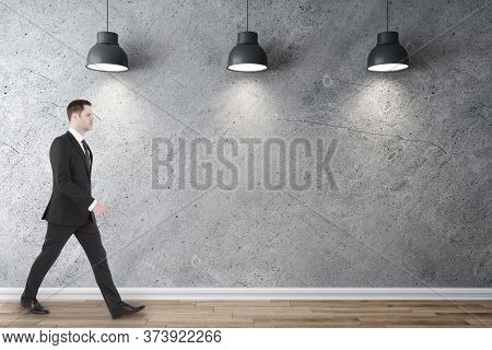 Businessman Walking In Gallery Interior With Three Ceiling Lamps And Blank Concrete Wall. Gallery Co