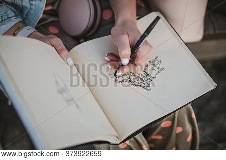 Sketchbook With A Drawing Of A House Close-up. Girl Draws With Her Left Hand.