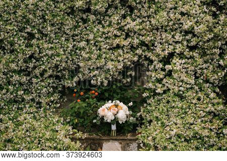 Bridal Bouquet Of White Peonies, Cream Roses, Orange Buttercups And Branches Of Eucalypt Tree On By
