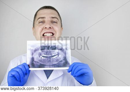 A Dentist Doctor Examines A Radiography Of The Teeth Of A Patient Who Has Problems And Teeth Are Ins