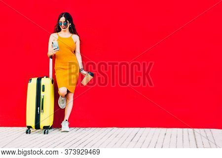 Traveling Woman With A Yellow Suitcase Using A Smartphone And Drinking A Coffee
