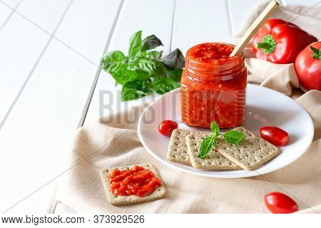 Balkan Traditional Dish Ajvar, Lutenitza, Pingjur, With Bread On A Plate On White Wooden Table. Serb