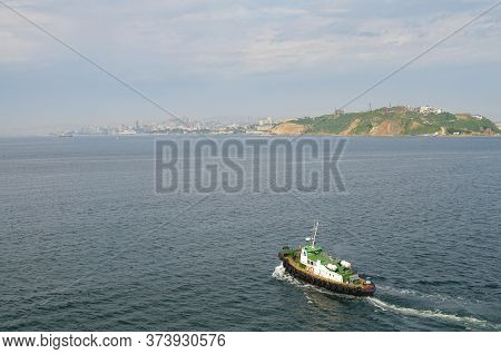 Tugboat In The Sea Against The Backdrop Of The Cityscape. Tugboat Await Large Cargo Ship To Assist T
