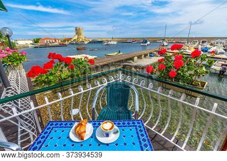 Scenic Landscape Of Red Geraniums Flowering And Breakfast With Croissant And Cappuccino In Italian C