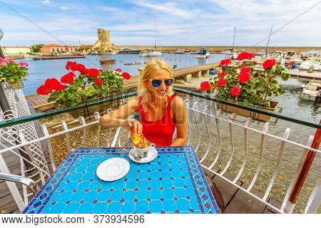 Woman In Red Dress Heaving Breakfast With Croissant And Cappuccino In Italian Cafe. Scenic Landscape