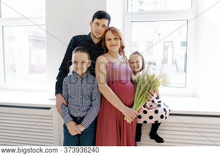 Happy Family Portrait At Home. Parents, Pregnant Mother And Father With Lovely Two Kids. Happy Frien