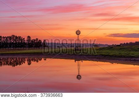 Windmill Sits On Farm Land Near A Dam With Beautiful Sunrise Sky And Water Reflections.  A Bird Sits