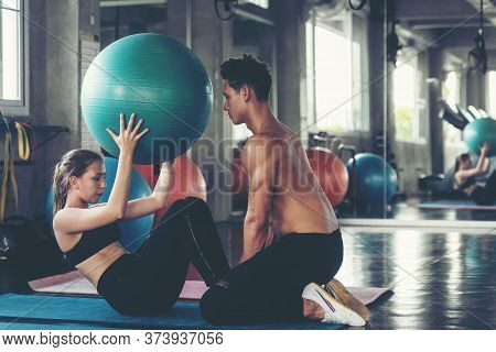 Trainer Training Yoga Ball And Exercise With  Woman At The Gym For Healthy Care And Body Slim.  Fitn