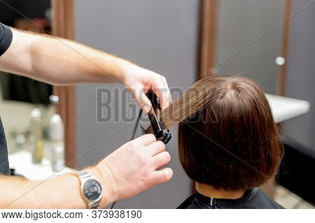 Hairdresser Hands Are Straightening Hair Of Woman With Straightener Tool In Hair Salon, Back View.