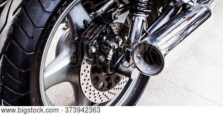 Back Of Sports Bike Close-up In Garage. Wheel, Brake Disc, Exhaust Pipe, Transmission, Shock Absorbe