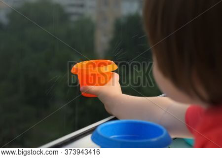 Child Catching Rain Drops. Staying At Home Concept. Rainy Day, Catching Water Drops With Plate. Happ