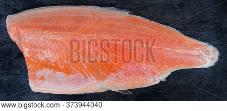 Trout Fillet On The Skin As A Boneless Half Of The Fish Lies Skin Side Down On The Black Surface