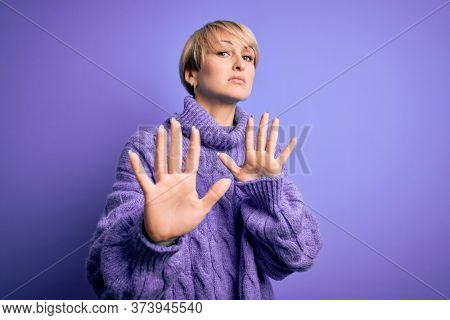 Young blonde woman with short hair wearing winter turtleneck sweater over purple background Moving away hands palms showing refusal and denial with afraid and disgusting expression. Stop and forbidden