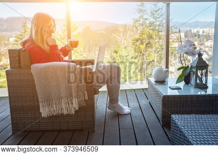 Stay at home, working in house. Woman spend free time on terrace in home clothes. Work with laptop and drinking tea. Beautiful mountain views in sunny day. Holidays time.