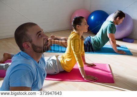 Yoga instructor with students practicing cobra pose in health club