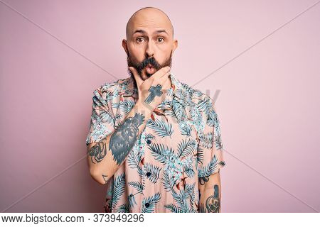 Handsome bald man with beard and tattoo wearing casual floral shirt over pink background Looking fascinated with disbelief, surprise and amazed expression with hands on chin