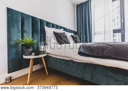 Cozy bedroom with comfortable bed in modern studio apartment. Interior design