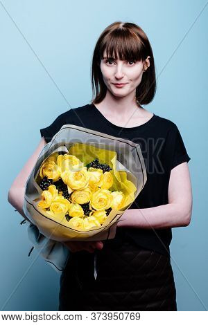 Portrait Of Young Female Florist With Bouquet Of Flowers In Transparent Package In The Hands On A Bl