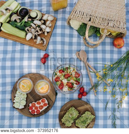 Top View Of Picnic Basket With Healthy Vegan Sandwiches On Blue Checkered Blanket In Park. Fresh Fru