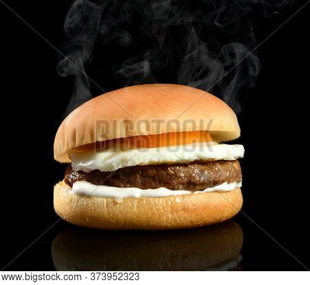 Fresh Tasty Hot Steamy Burger With Beaf Meat Cutlet Fried Egg And White Sauce Mayonnaise Over Black