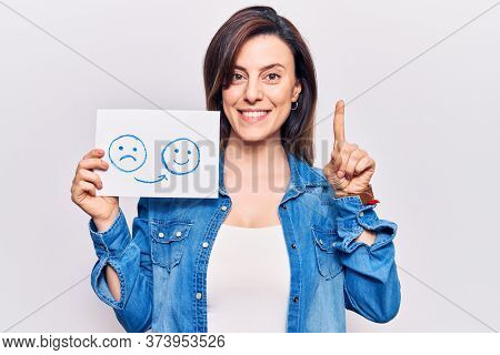 Young beautiful woman holding sad to happy emotion paper smiling with an idea or question pointing finger with happy face, number one