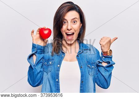 Young beautiful woman wearing doctor uniform holding heart pointing thumb up to the side smiling happy with open mouth