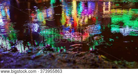 Puddle at night in the rain with reflecting lights at a fair or fun fair