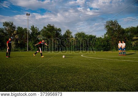 Soccer Player Kicks The Ball.soccer Player Takes The Free-kick.
